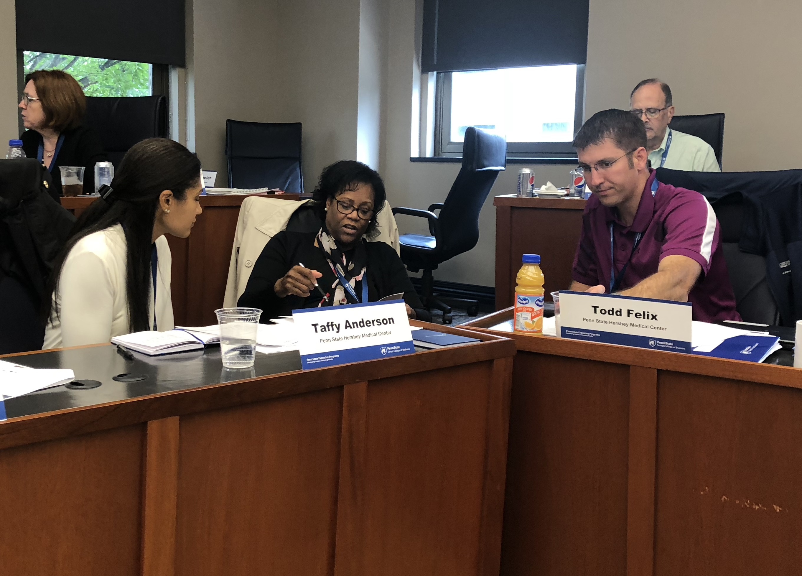 Dr. Taffy Anderson, Dr. Dorothy Rocourt and Dr. Todd Felix sit behind a desk and confer on a classroom assignment during the Leadership Academy.