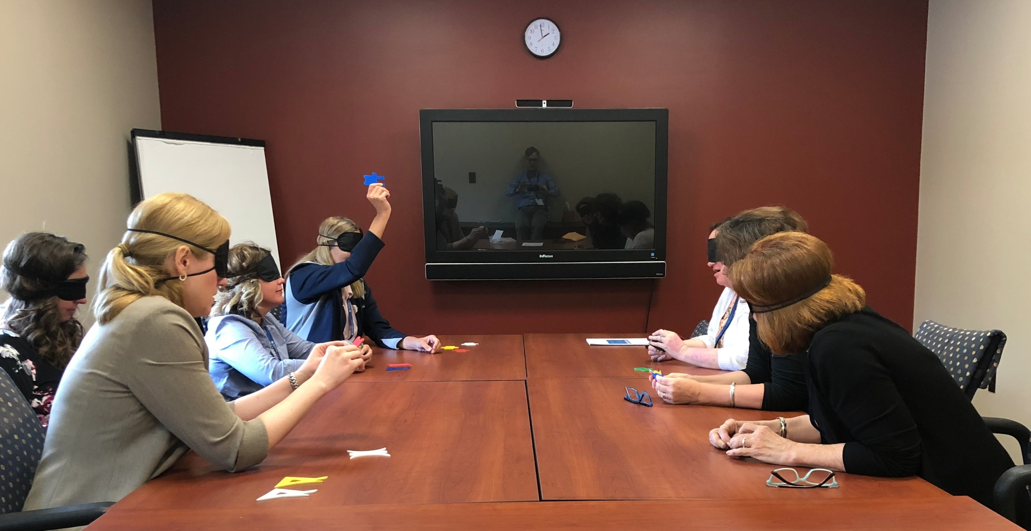 Six Leadership Academy attendees sit across from each other at a conference table, blindfolded, as they participate in an interactive session designed to promote teamwork. One blindfolded woman holds a piece of paper in the air as the others lean forward to hear her speak. A large screen TV and a whiteboard can be seen in the room.