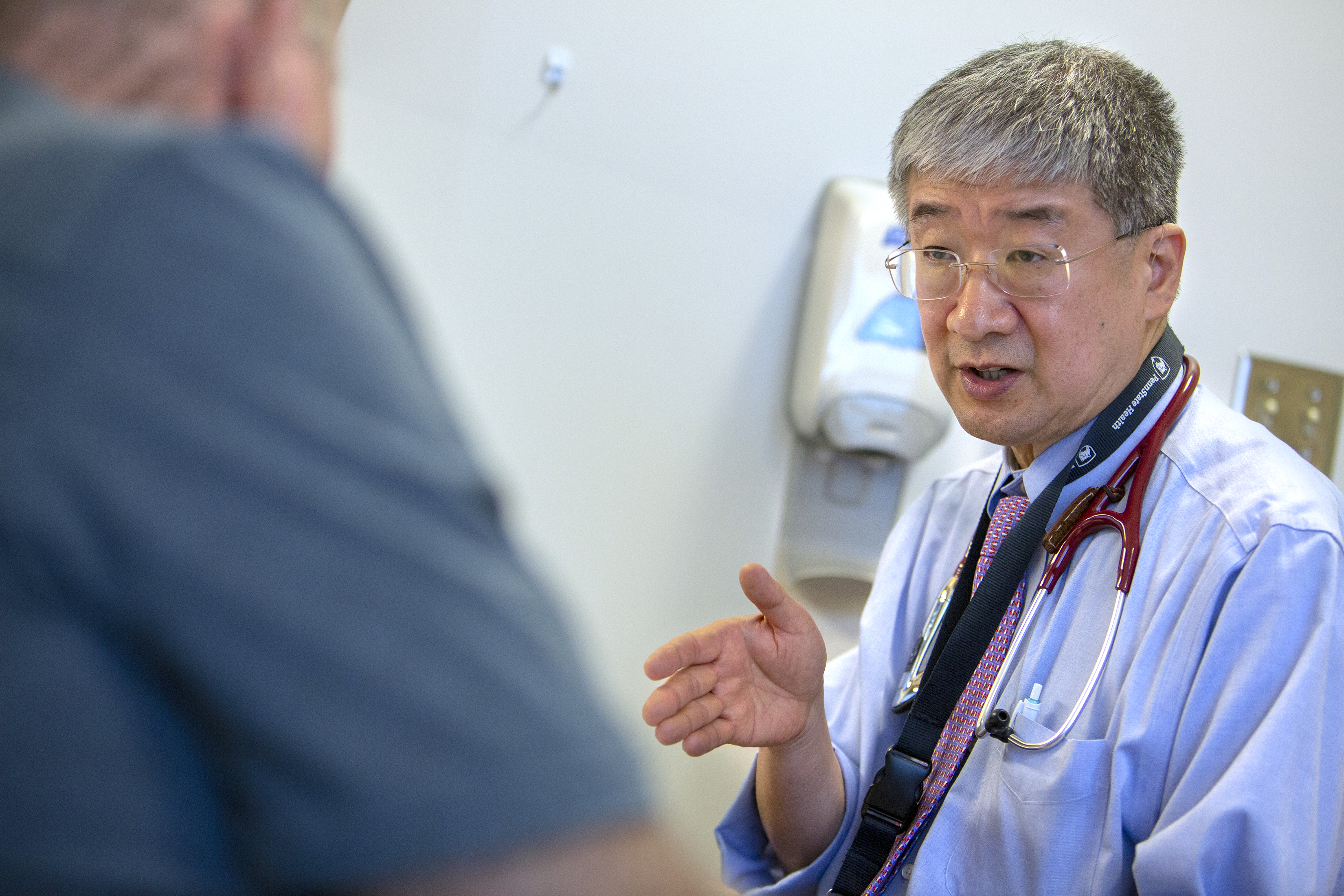 Dr. Shin Mineishi of Penn State Cancer Institute gestures while talking to an older male patient in an exam room. He is wearing a stethoscope around his neck, a shirt, tie, a lanyard and glasses. Behind him is a hand sanitizer machine. The patient is out of focus, and his head and right shoulder are visible.