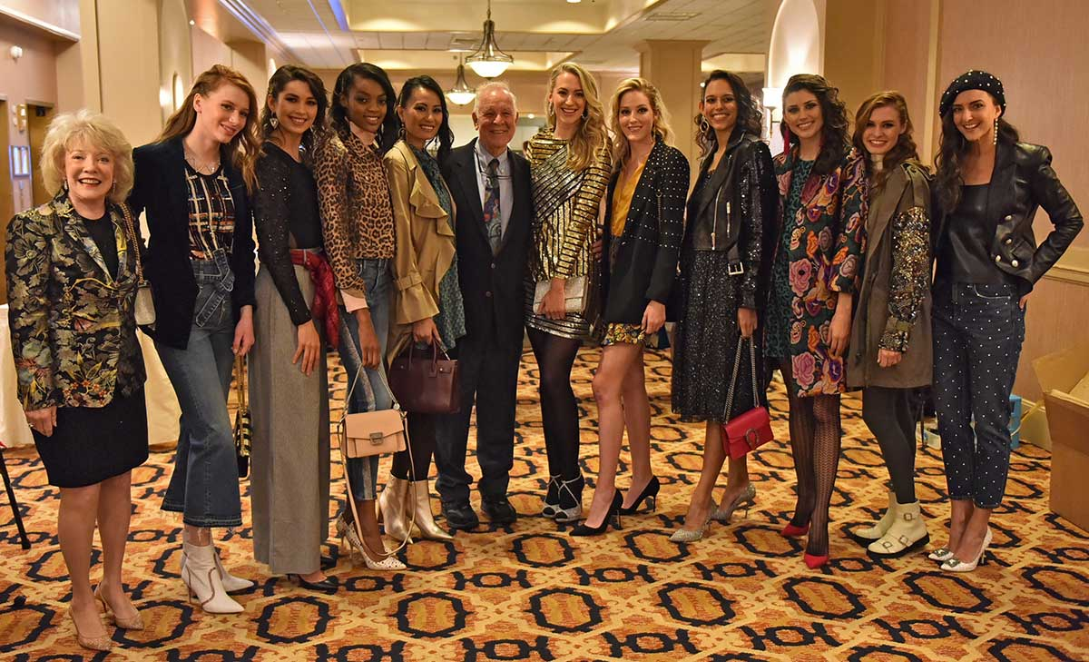 Jeanne and Ed Arnold smile with 10 models at the 2018 Neiman Marcus Runway Show. The models wear a variety of fashions and stand in a row on an ornate carpet.