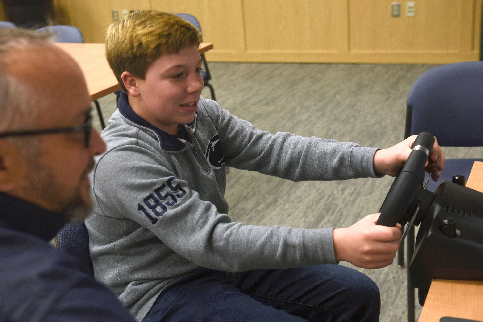 A teen boy smiles and holds the wheel of the driving simulator One Simple Decision. Next to him is a man with glasses, gray hair and a beard. Behind them are a table and chairs, carpet and a wooden cabinet.