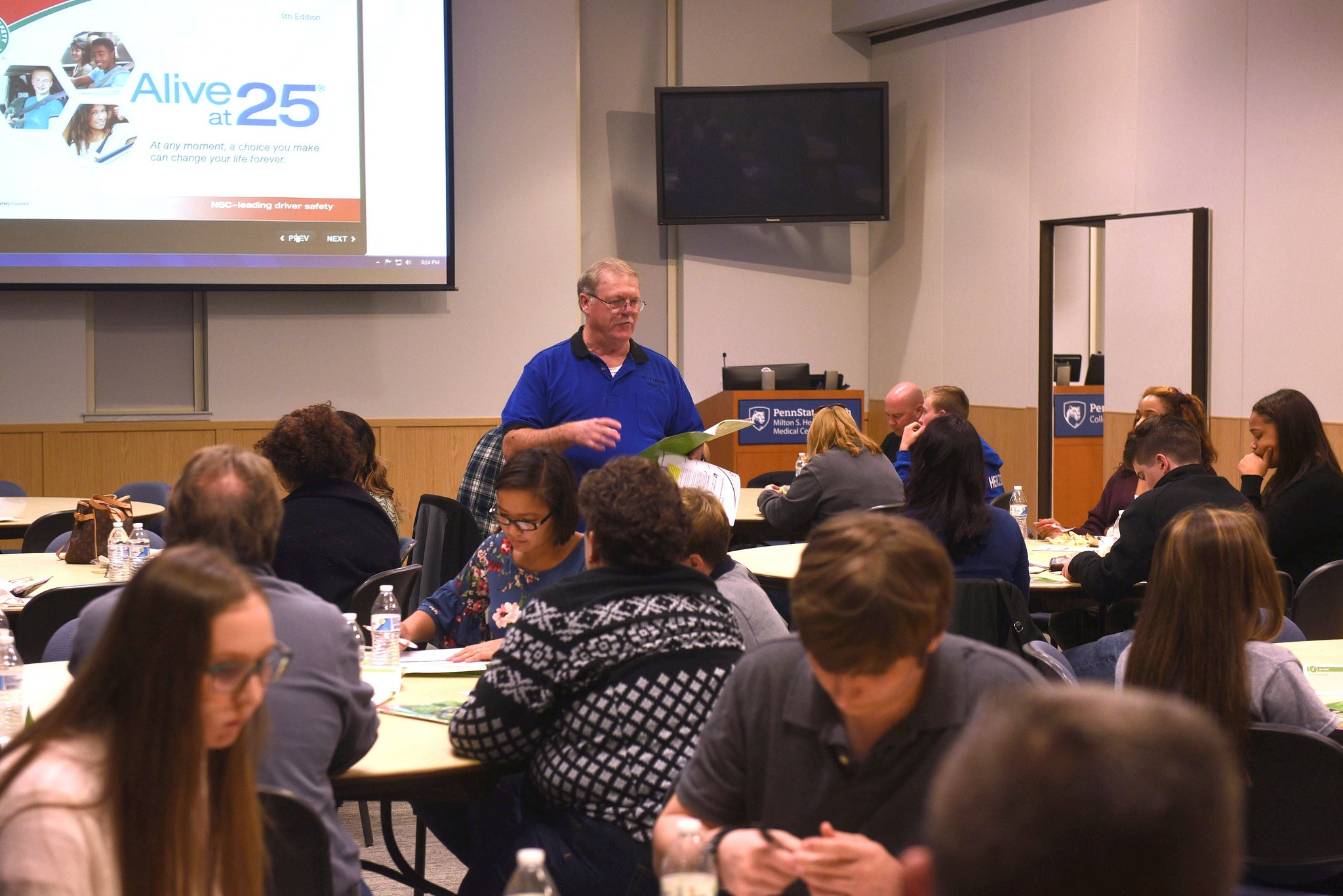 """Robert Gilmer, an Alive at 25 instructor, stands in front of a group of teens and parents who are sitting at round tables and looking down at their phones. Behind him is a screen with a PowerPoint slide with the text """"Alive at 25."""""""