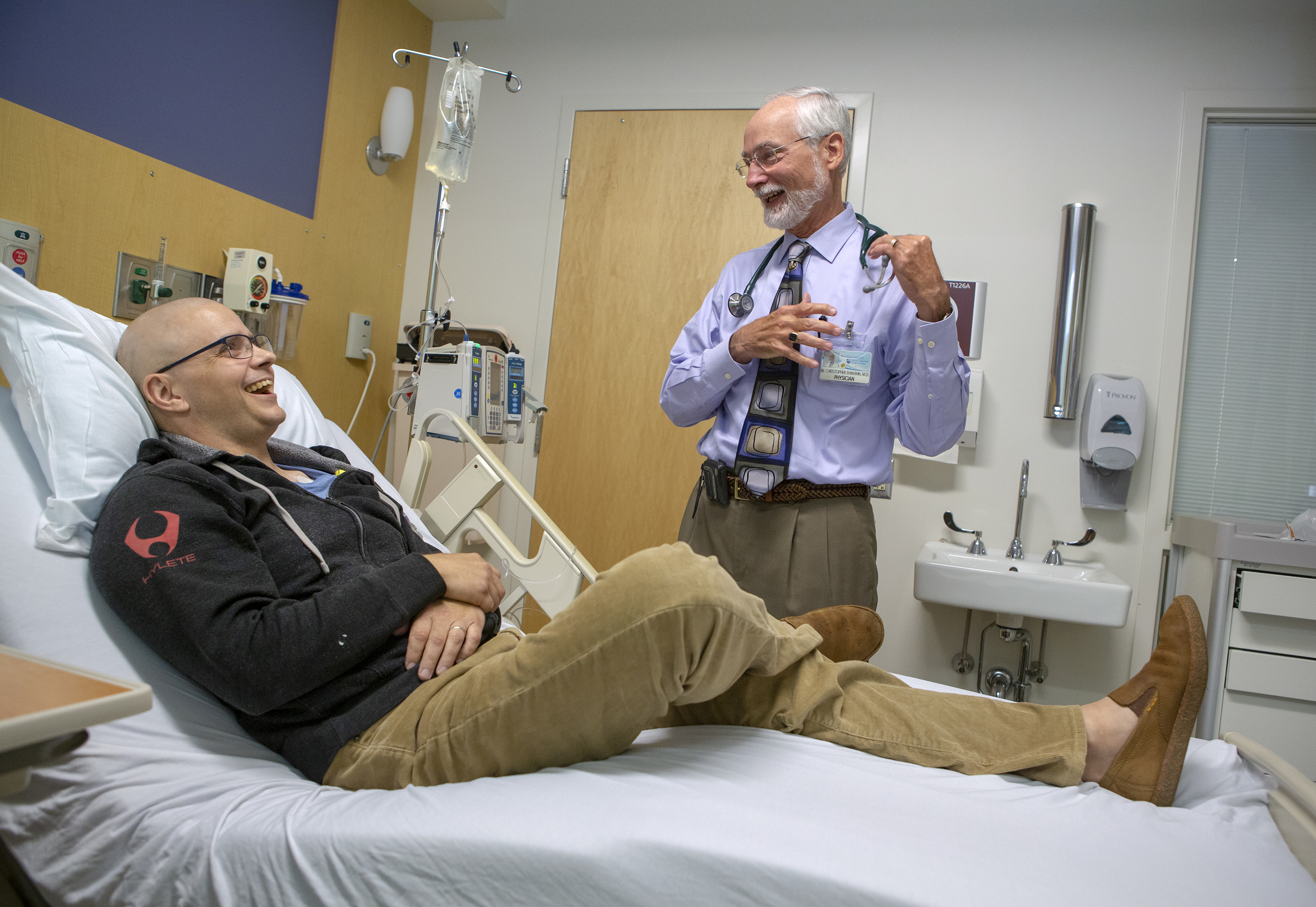 Tim Card and Dr. Christopher Ehmann smile. Tim is sitting propped up in a hospital bed wearing glasses and dressed in a sweatshirt, corduroy pants and shoes. An IV bag is Dr. Ehmann has a beard and is wearing shirt, tie, khaki pants and an ID badge and has a stethoscope around his neck.