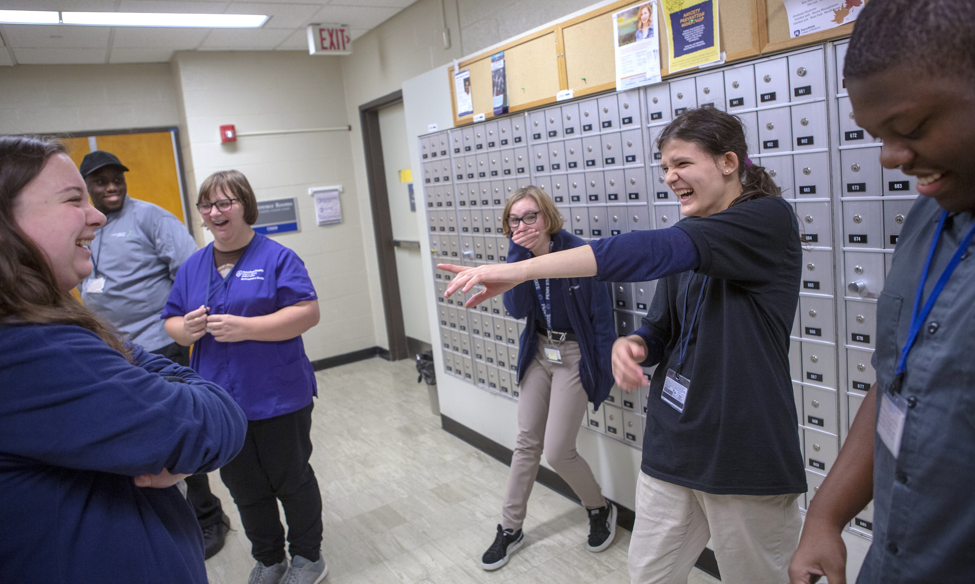 Project Search students play an icebreaker game in the hallway outside their classroom at Penn State Health. Metal mailboxes and bulletin boards line the side of the hall. Cheyanne Wilson laughs and points at Emily Swanic, who is laughing with her arms crossed over her chest. Ava Pyles covers her mouth with her hand as she laughs, while James Silver, Samantha Brace and James Morrison look on.