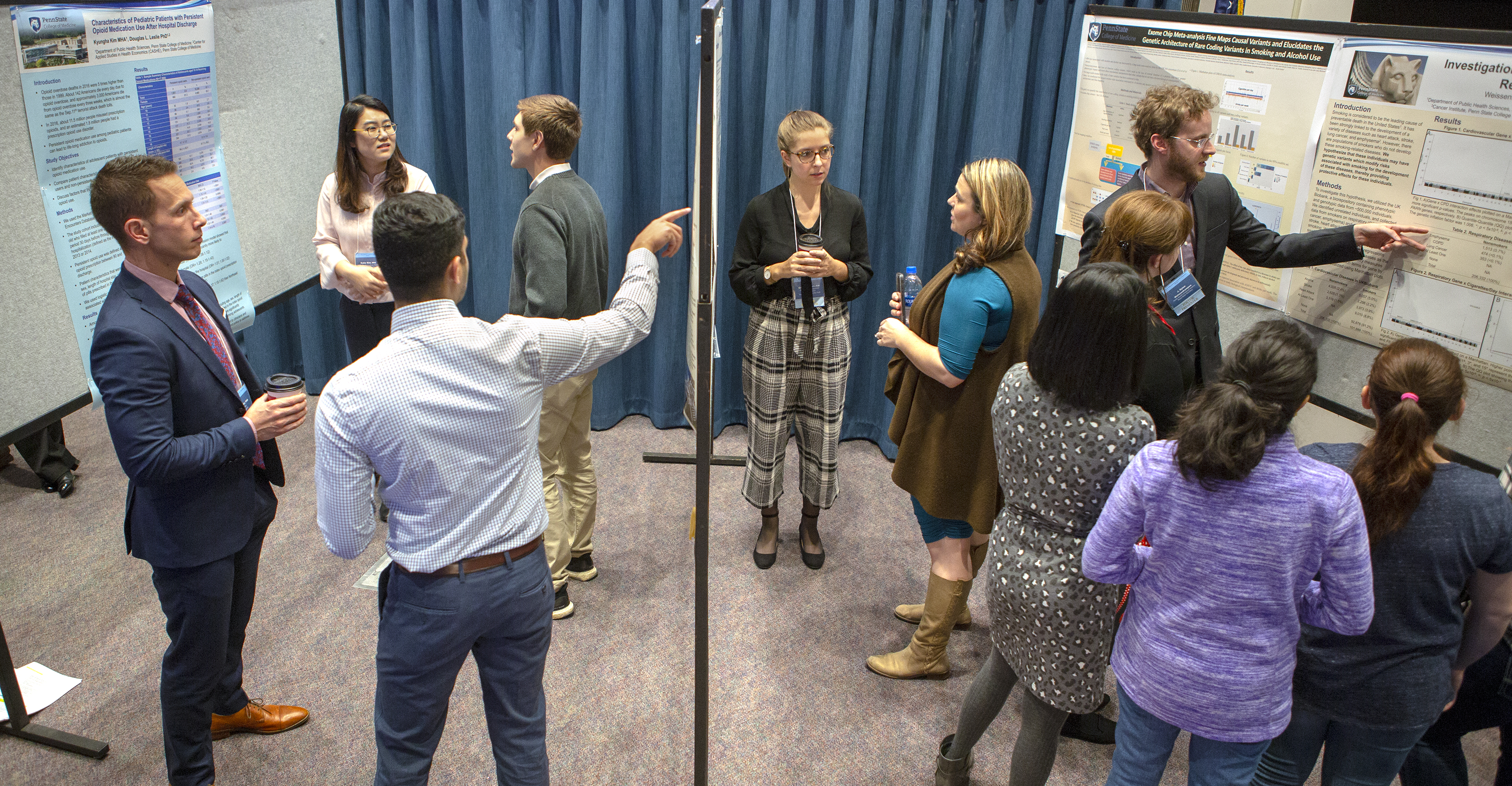 A room with three panels holding scientific posters is filled with men and women. They are pointing to the information on the posters and discussing the research in groups. A blue curtain forms the background of the room.