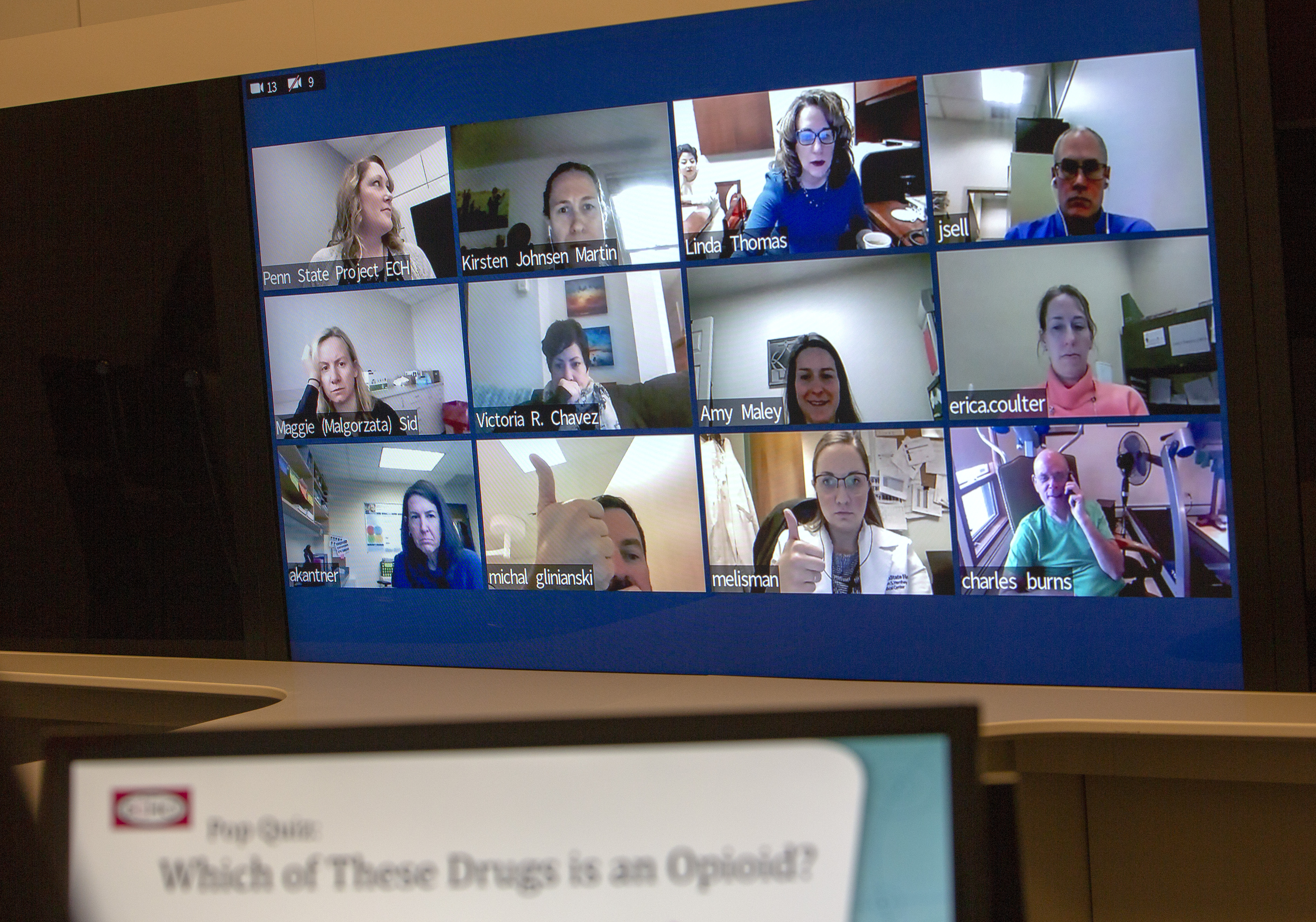 "A large screen contains 12 mini screens showing physicians participating in Project ECHO. The participants are looking into their own web cams as they participate in the session; some are smiling and giving a thumbs up while others are serious. In the foreground, an out-of-focus screen reads ""Pop Quiz: Which of these drugs is an opioid?"""