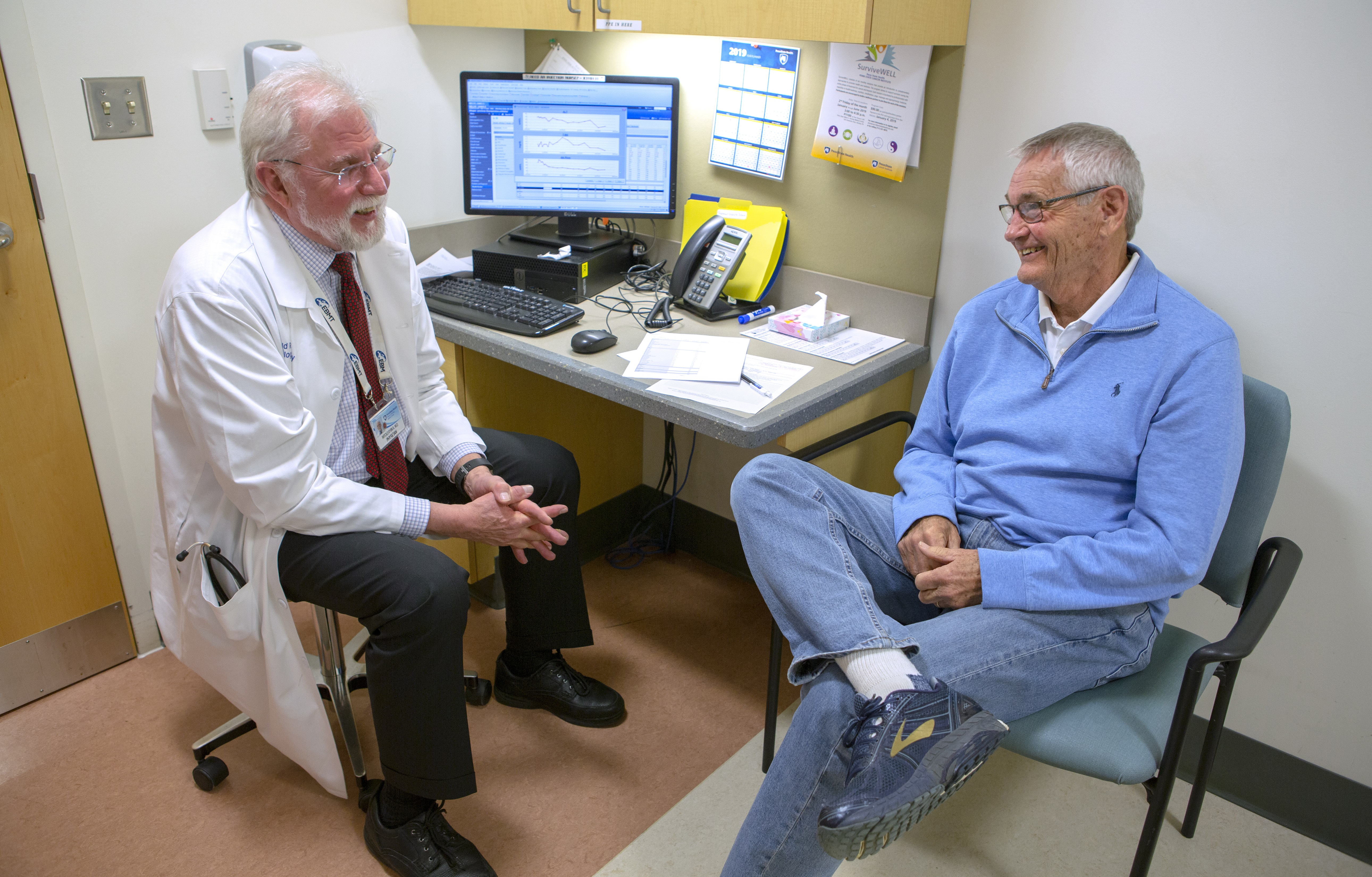 Jim Miller, right, smiles during a follow-up appointment with Dr. Witold Rybka at Penn State Cancer Institute. Miller is wearing a casual shirt, jeans and sneakers. He has gray hair and wears glasses. Dr. Rybka is wearing a lab coat, dress shirt, tie and dress pants. He has white hair, a beard and glasses. Beside them is a table with a computer, phone and papers.