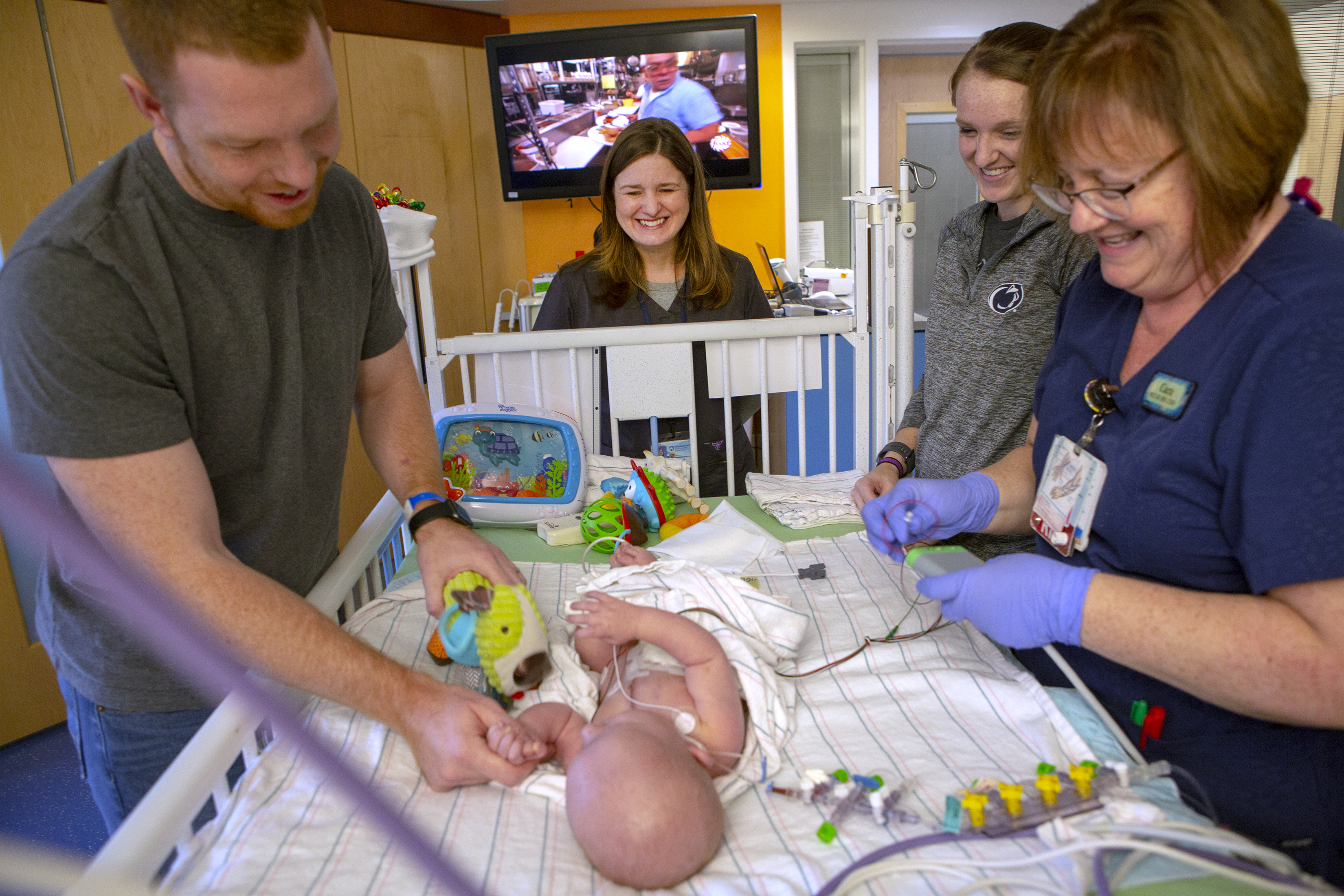 Deborah Berini smiles at the foot of a crib in the Pediatric Intensive Care Unit at Penn State Children's Hospital. PICU nurse Cara Kapaun, right foreground, attaches intravenous lines to a baby who is lying in the crib. The father, Zach Hoover, stands on the left, touching his son's hand and holding a toy. The mother, Rachel, smiles at her son. Behind them is a TV monitor with a program on it.