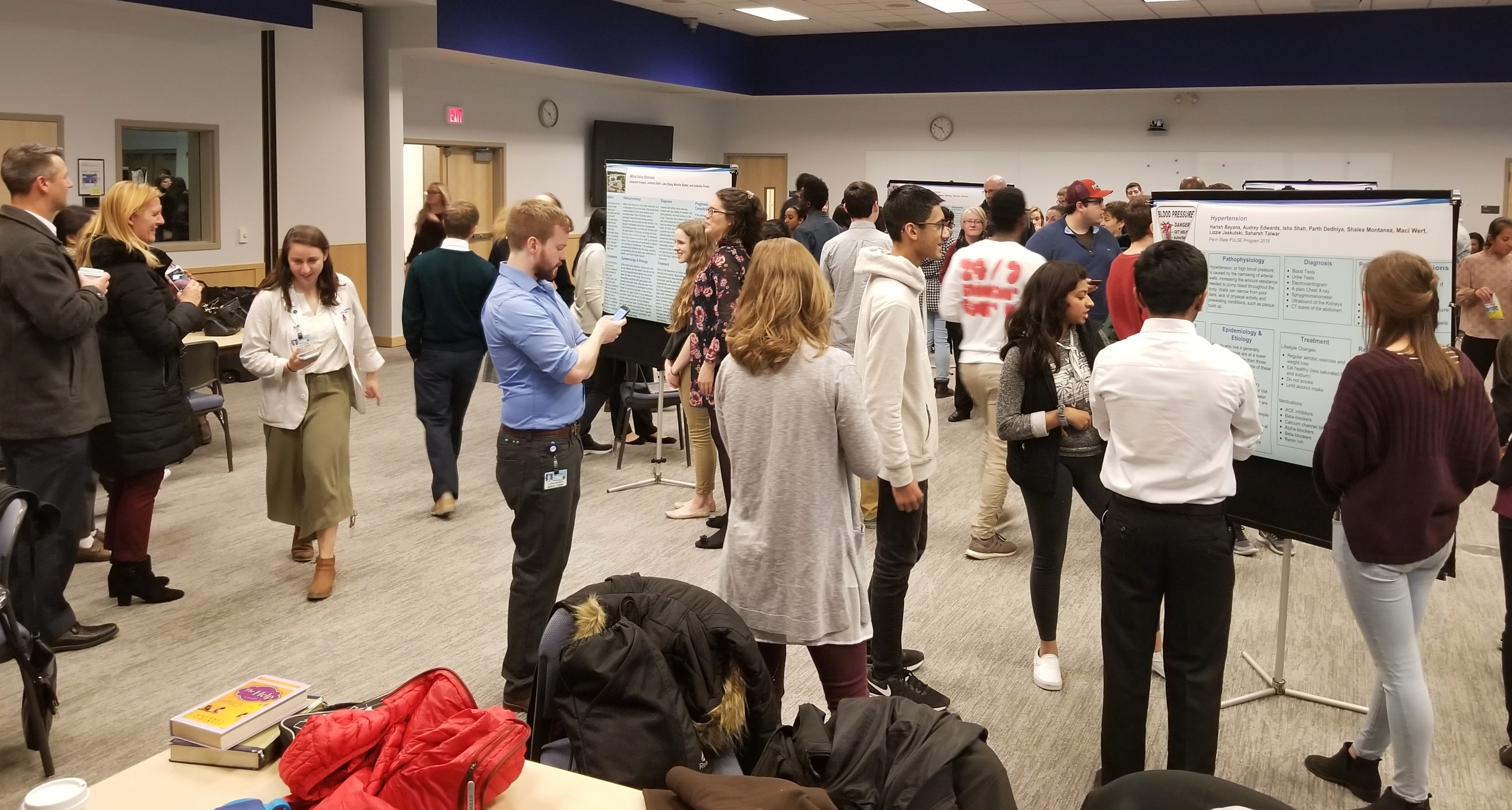 A group of approximately 40 high school students and adults look at different poster presentations during Penn State College of Medicine's PULSE program in 2018. The posters feature cardiology topics and are printed on large sheets of vinyl mounted on screens. The group is in a large conference room. A table and chairs with winter coats hanging on them are in the foreground.