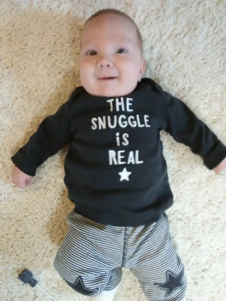 """A 45-day-old baby boy, Knoxley Himes, lies on a carpet and smiles at the camera. His sweatshirt reads """"The snuggle is real."""" His sweatpants have stars on the knees."""