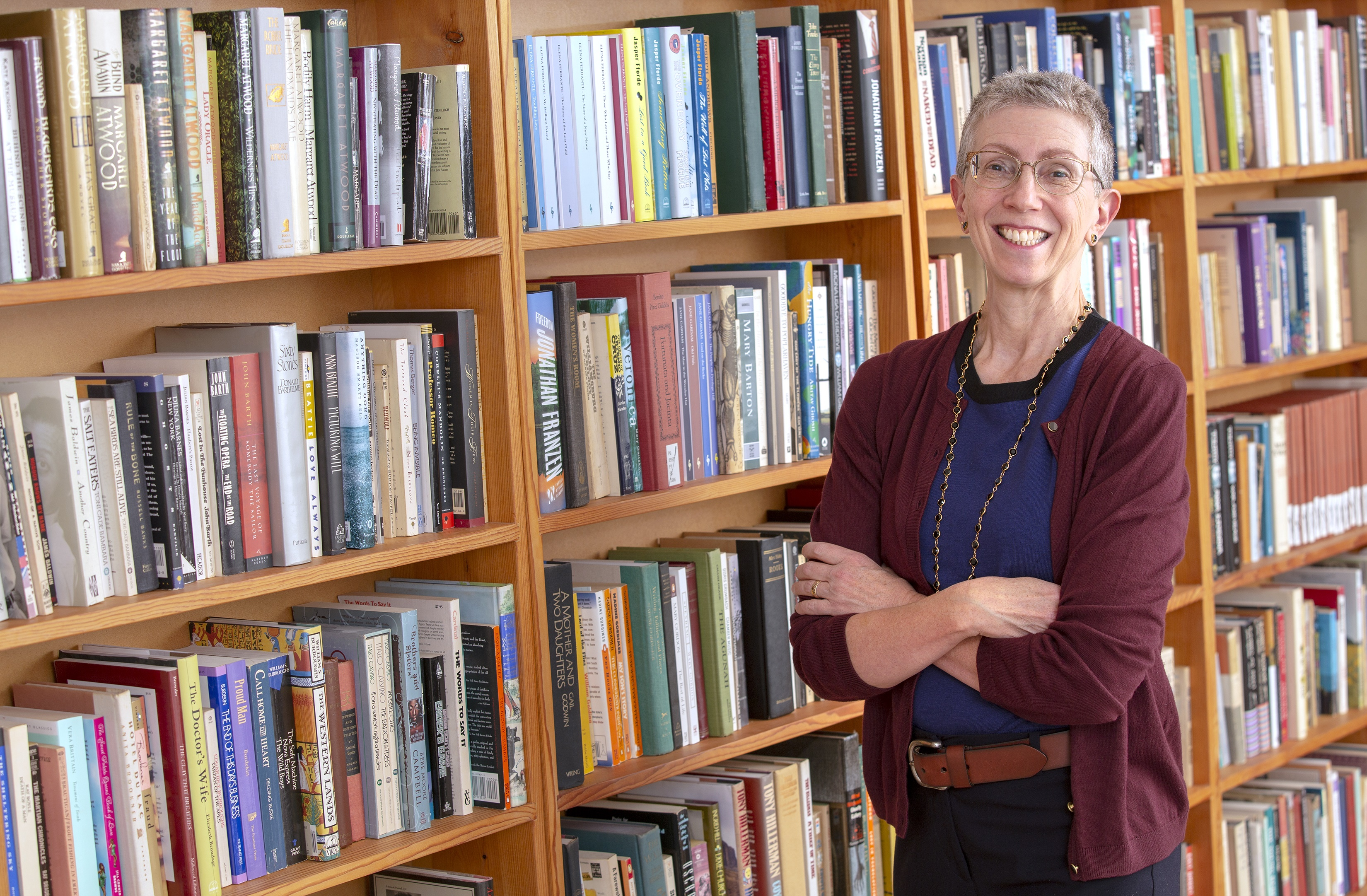 Bernice Hausman, chair of Penn State College of Medicine's Department of Humanities, stands in a library with her arms crossed and smiling. She has short, gray hair and is wearing glasses, a sweater, a T-shirt, casual pants and a brown belt. Five rows of bookshelves filled with books are to her left.