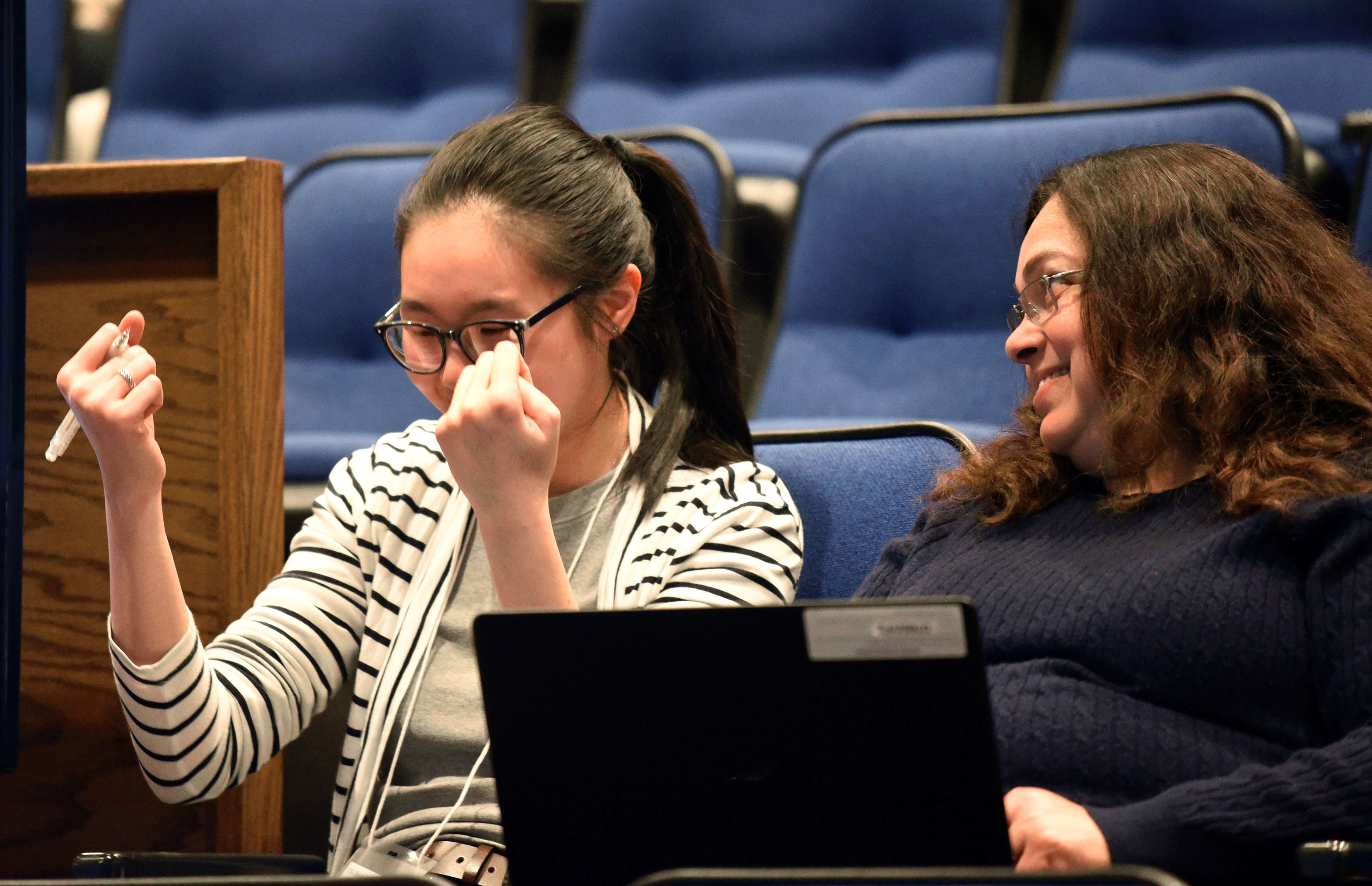 Kelly Chan, who wears a striped sweater and has glasses and her long hair in a ponytail, clenches both fists in victory as she celebrates a correct answer at the 2019 USA National Brain Bee, held April 12-14 at Penn State College of Medicine. Her proctor Dr. Vinita Acharya, associate professor of neurology at Penn State College of Medicine, looks over at her and smiles. The two are seated in auditorium seats. Archarya has long curly hair and is wearing a sweater and glasses and holds her laptop on her lap.