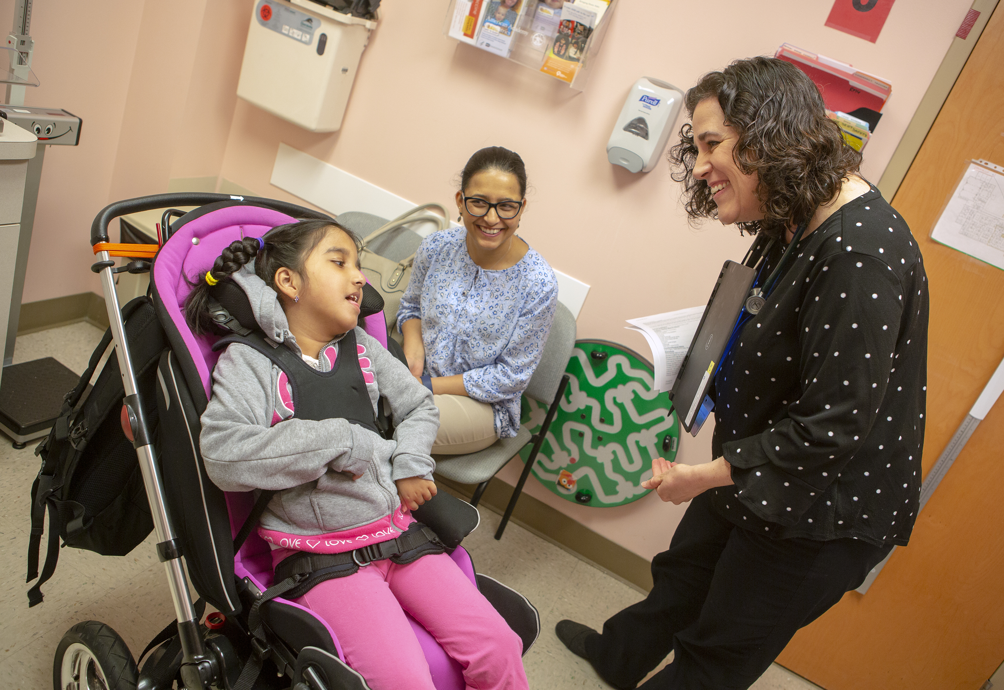 Dr. Laura Murphy, pediatrician with Penn State Children's Hospital's Pediatric Complex Care Program, smiles and bends down to greet her patient, Brinda Rizal, who is in a wheelchair. Brinda, who has braids and is wearing a sweatshirt and pants, is strapped into the wheelchair and looks up at Murphy, who is wearing a polka dotted shirt and pants and wears a stethoscope around her neck. Brinda's mother, Basudha Rizal, wearing glasses and a printed top and pants, is sitting in a chair against the wall. She smiles at her daughter. A soap dispenser, pamphlet rack and folders are hanging on the wall of the exam rom.