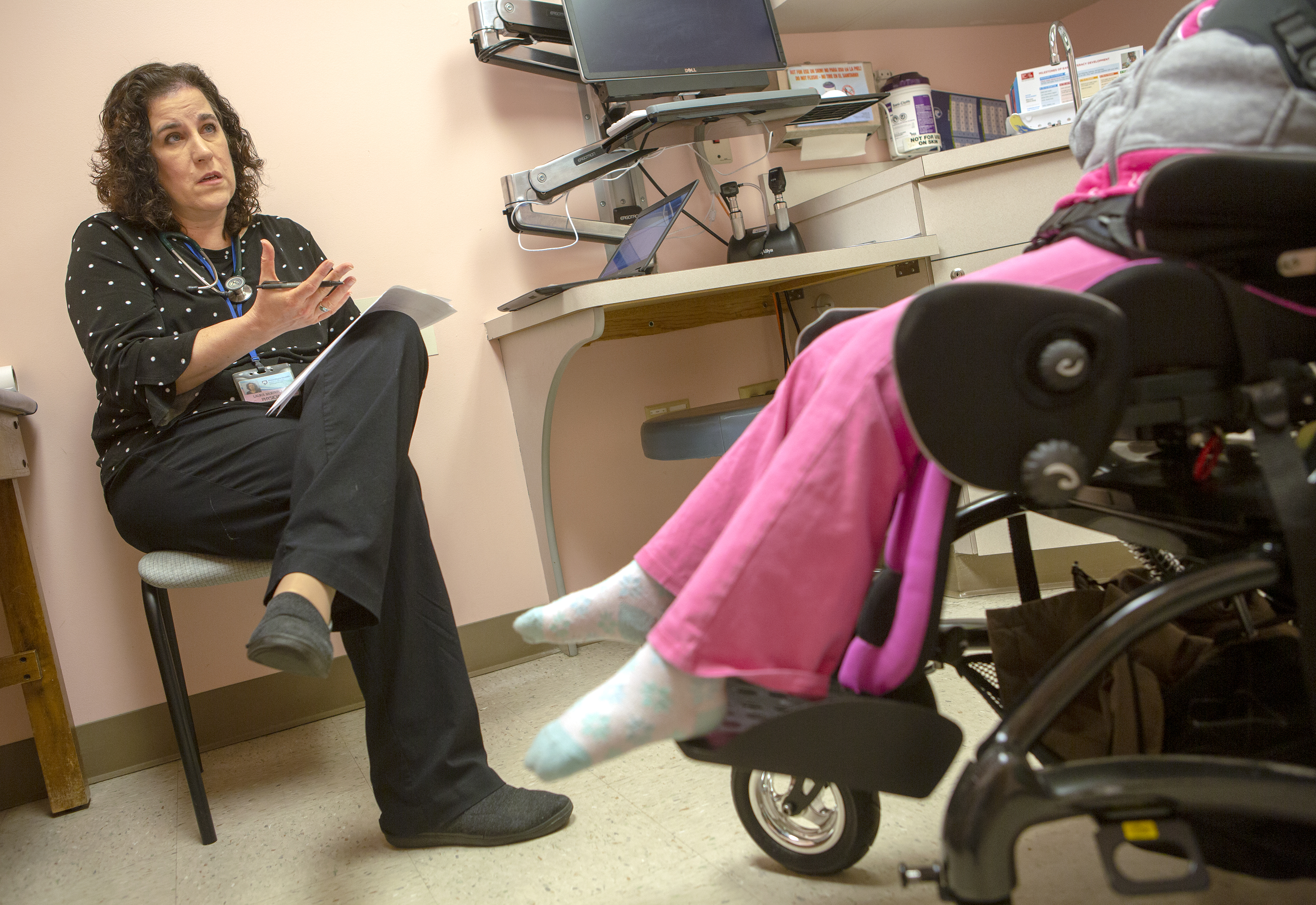 Dr. Laura Murphy is seated in a chair in an exam room and holds a pen in her hand and gestures as she talks with her patient, Basudha Rizal, 8, who is seated in a wheelchair. The wheelchair and Basudha's pants and socked feet are visible. Murphy has shoulder-length wavy hair and wears a polka dotted shirt and pants. A computer screen atop a small desk and a counter with sink are in the background.