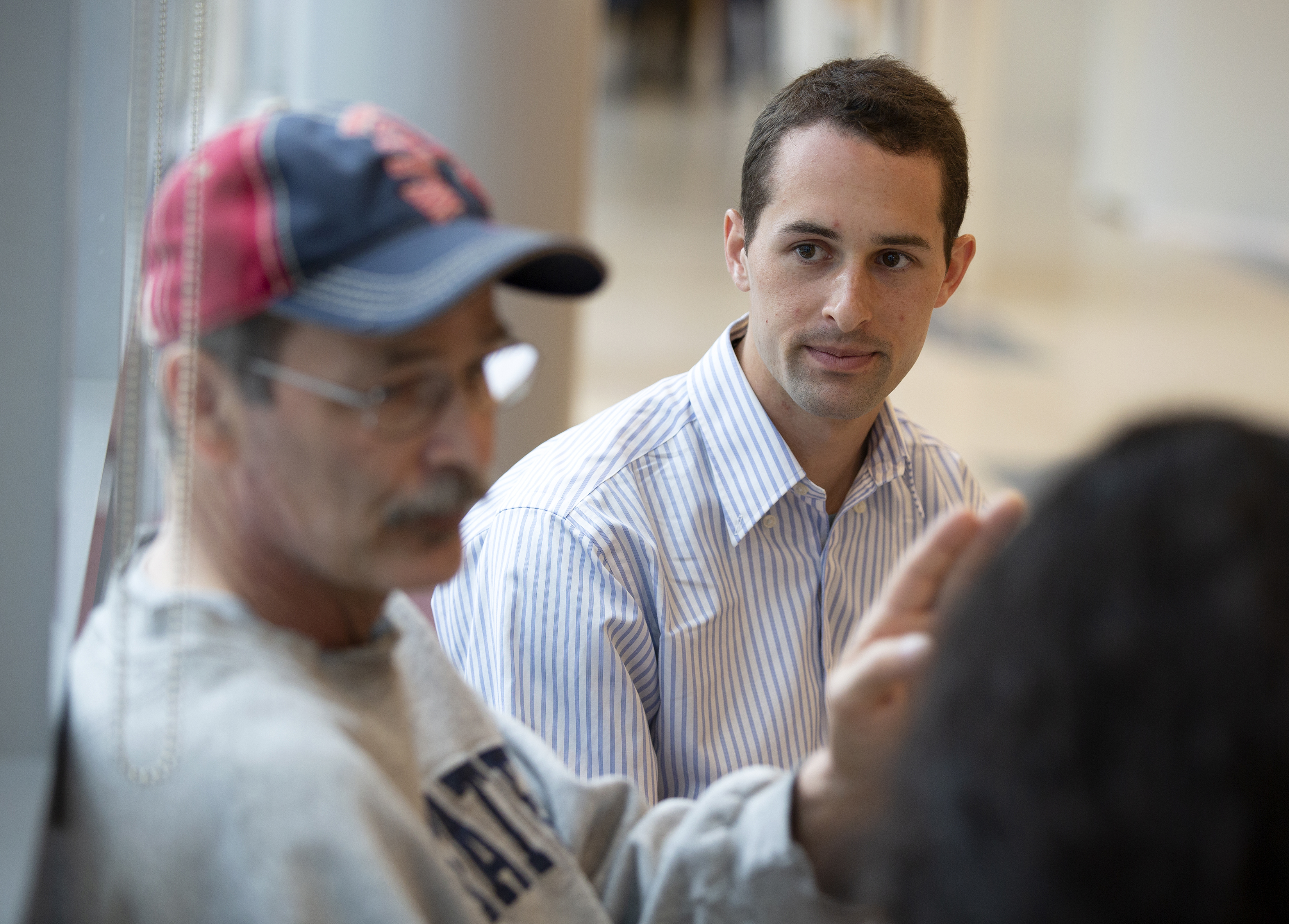 Timothy Groh, a first-year medical student, looks at Yancy Nauman as he talks, before Nauman goes in for chemotherapy treatment at Penn State Cancer Institute. Groh is in his 20s, has short hair and is wearing a striped dress shirt. Nauman is wearing glasses, a baseball cap and a sweatshirt. He is gesturing toward another person who is seen from behind. A clear plastic curtain is behind him.