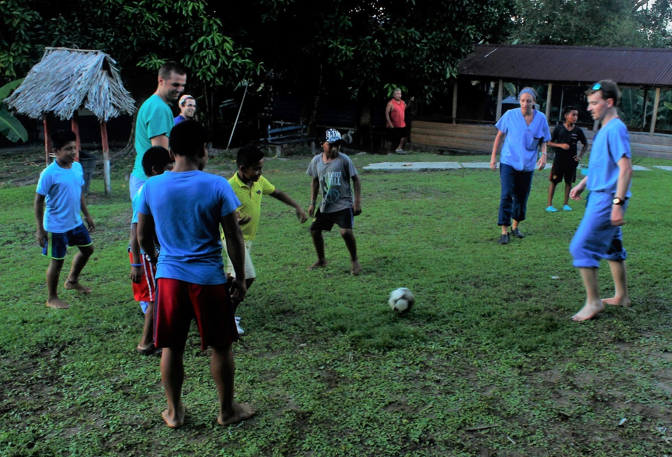Medical students Maddie Fritsche, second from right, and Andrew Nevin, right, take a soccer break with boys the Bocas del Toro province. Five boys and a male medical student are in front of them. One boy is about to kick the ball. A thatched hut and a pavilion with a proof are behind them.