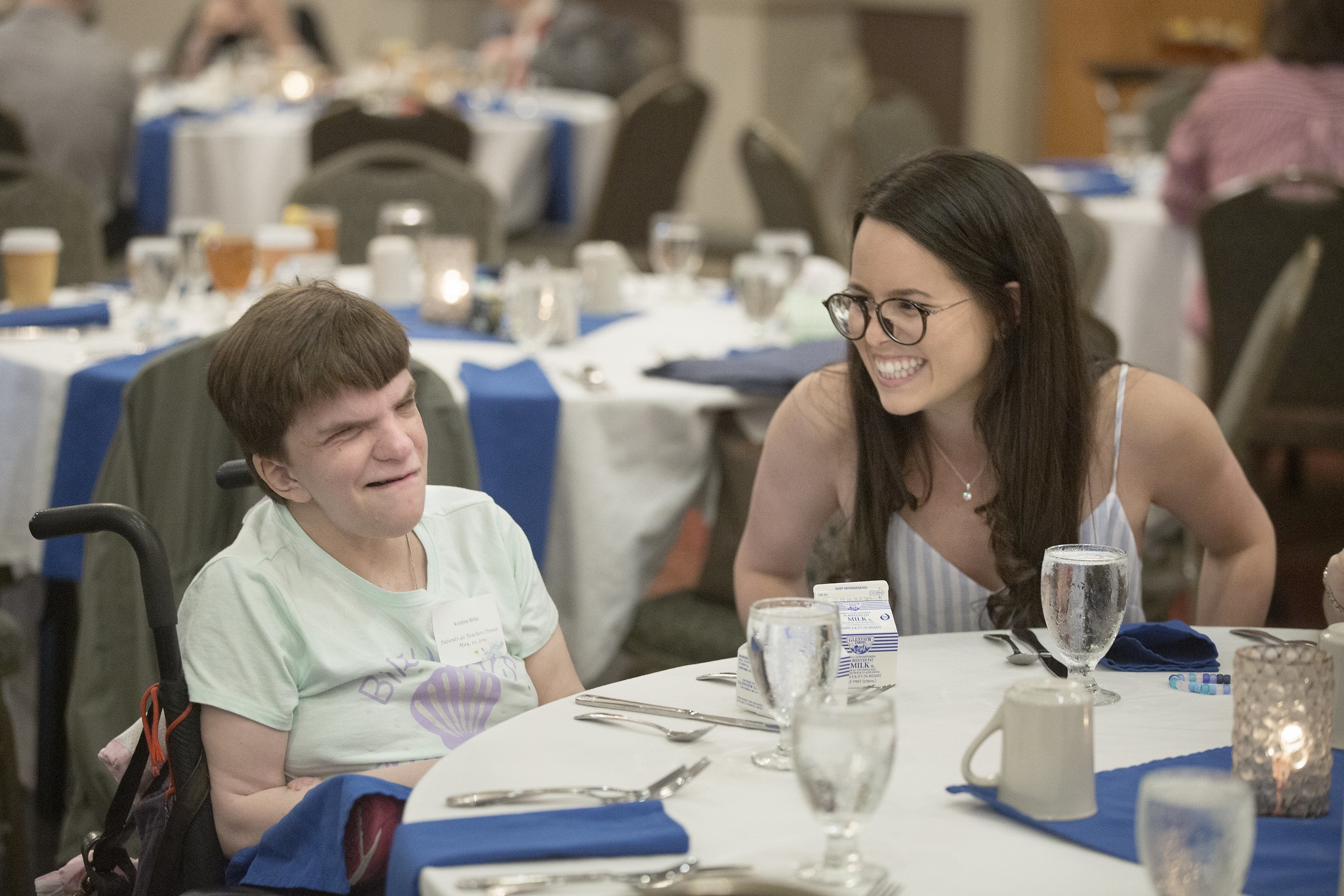 Medical student Daniela Medina, right, smiles at her patient teacher, Kristine Miller, at the Patients as Teachers recognition dinner in May 2019. Medina is wearing glasses and a strapless sundress. Miller has short hair and is seated in a wheelchair and wearing a T-shirt and nametag. Silverware, napkins and glasses are on the table in front of them.