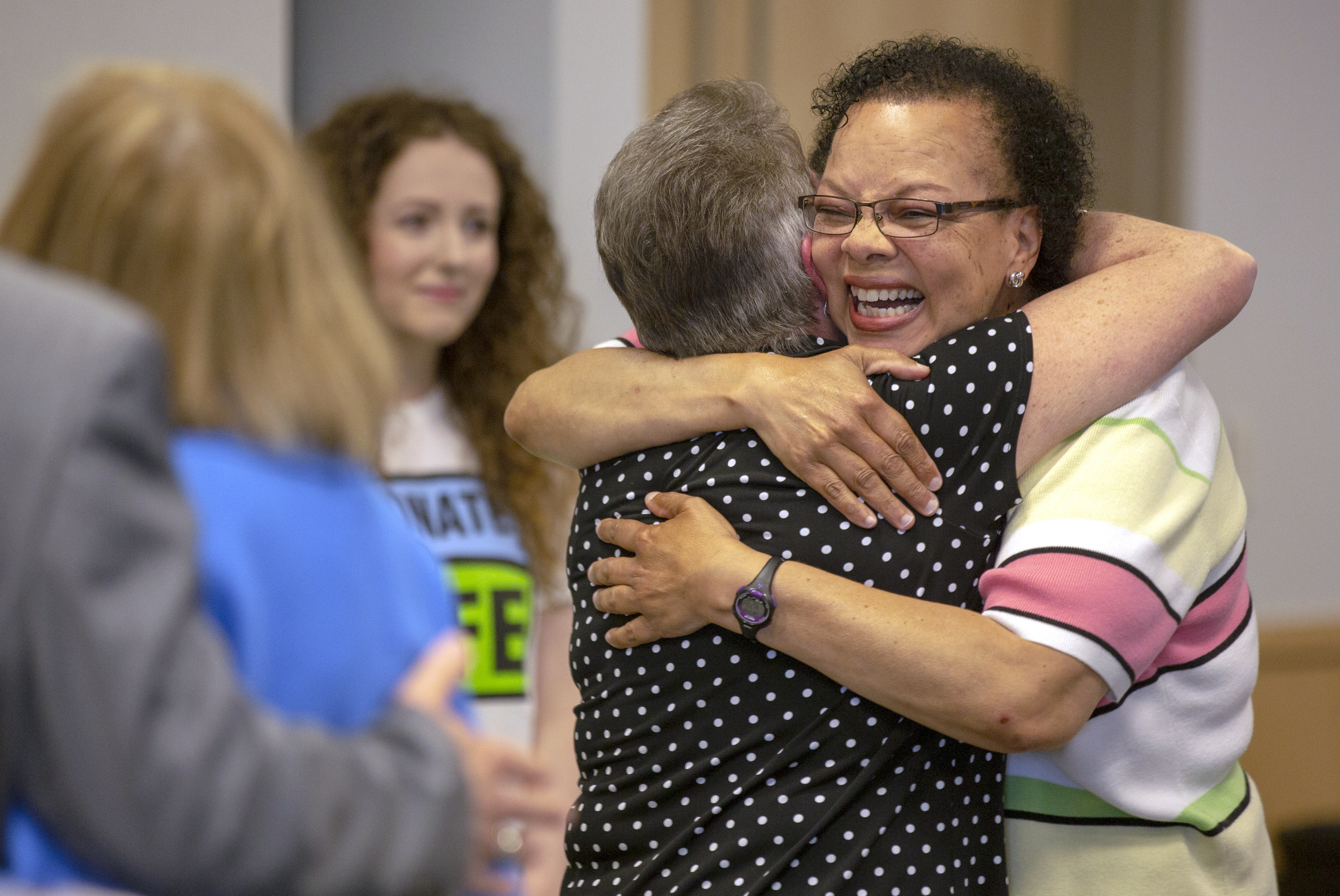 "Jeanette Bennett, right, embraces Gerry Paris. Jeanette is smiling and wearing glasses and a striped sweater. Gerry has her back to the camera and is wearing a polka-dot top. A woman with a ""Donate Life"" T-shirt is in the background. A woman with a blue blazer and a man's arm around her are on the left."