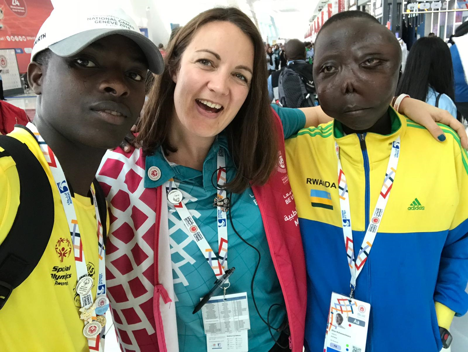"A woman wearing a red vest poses for a photo with two male Rwandan soccer players. The player on the right has a deformed face and is wearing a sweatshirt with the text ""Rwanda"" on the left. The player on the left is wearing a baseball cap and a Special Olympics T-shirt."