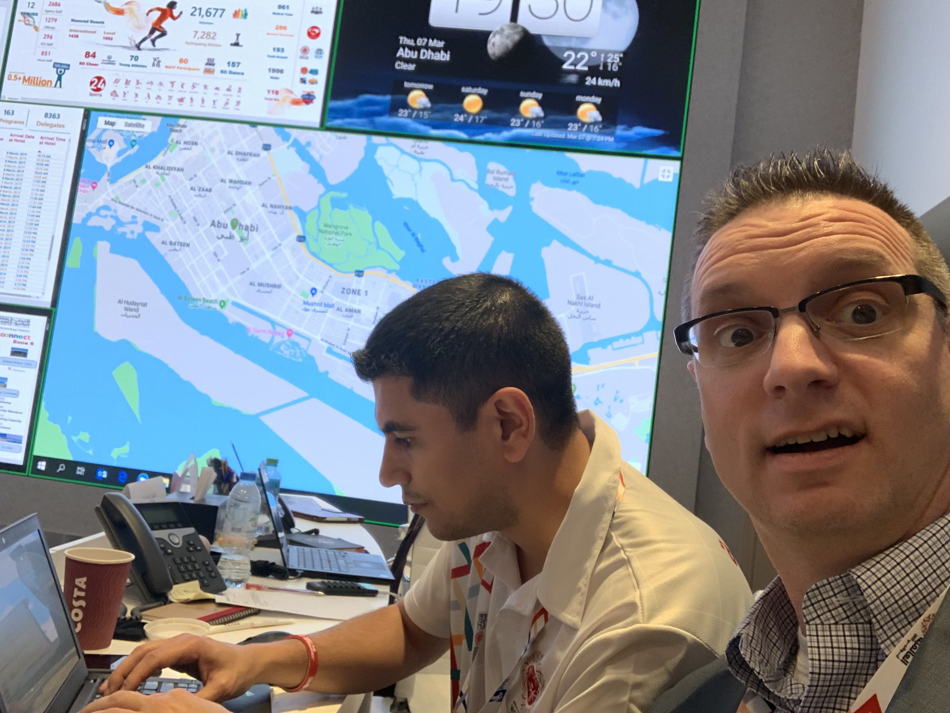 Dr. Seidenberg makes a comical face while sitting next to Dr. Samir Zeynalov, Special Olympics' medical operations manager, who is typing on a laptop. Behind them are maps on a screen. Zeynalov is wearing a white Oxford shirt and a lanyard.