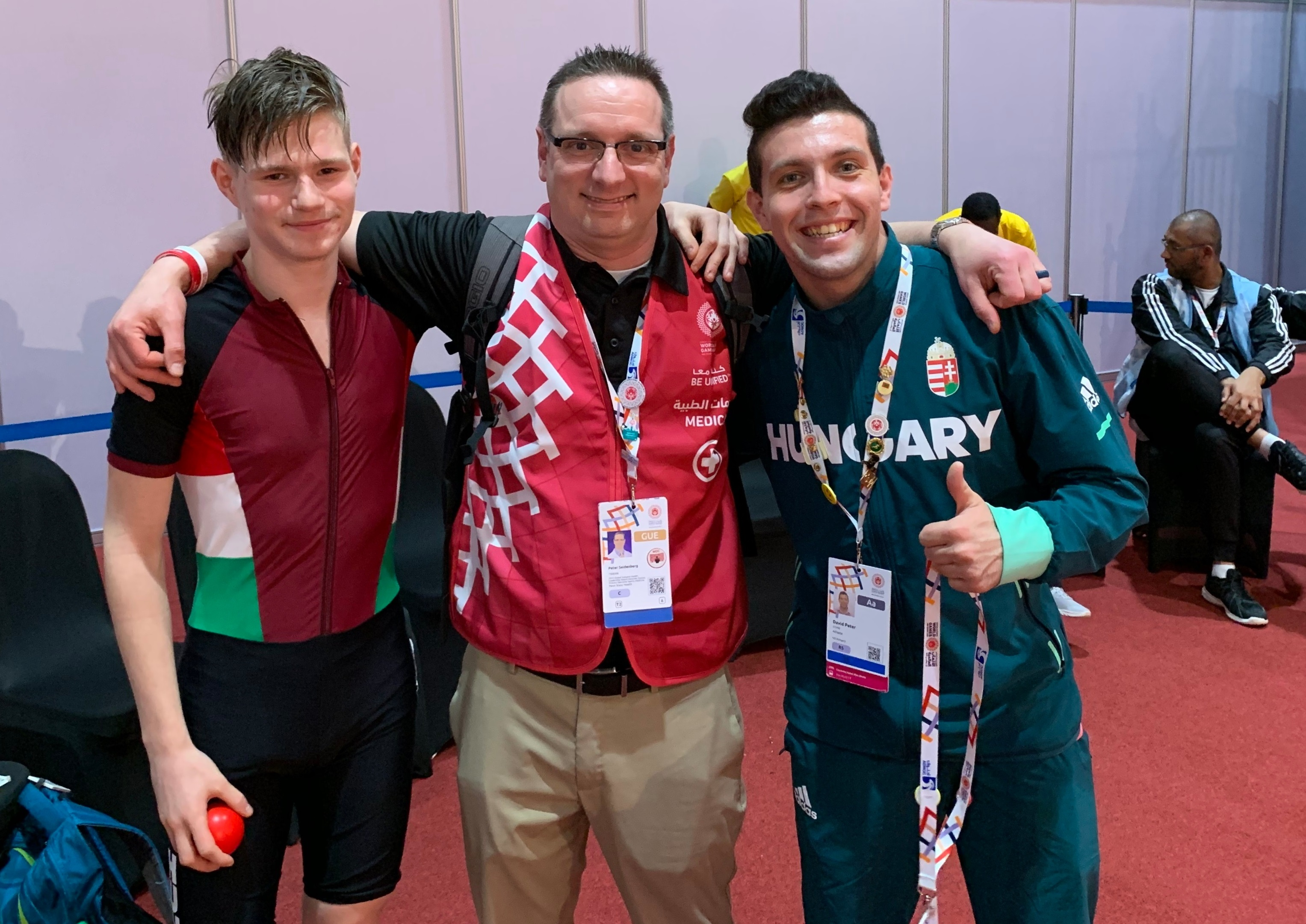 "Dr. Peter Seidenberg poses for a photo with two young men who are members of the Hungarian roller skating team. He is wearing a red vest with ""Medic"" on the right side. The player on the left is wearing a spandex suit with shorts. The player on the right is wearing a sweatshirt with ""Hungary"" on the front. Behind them are three players. One is sitting on a chair."