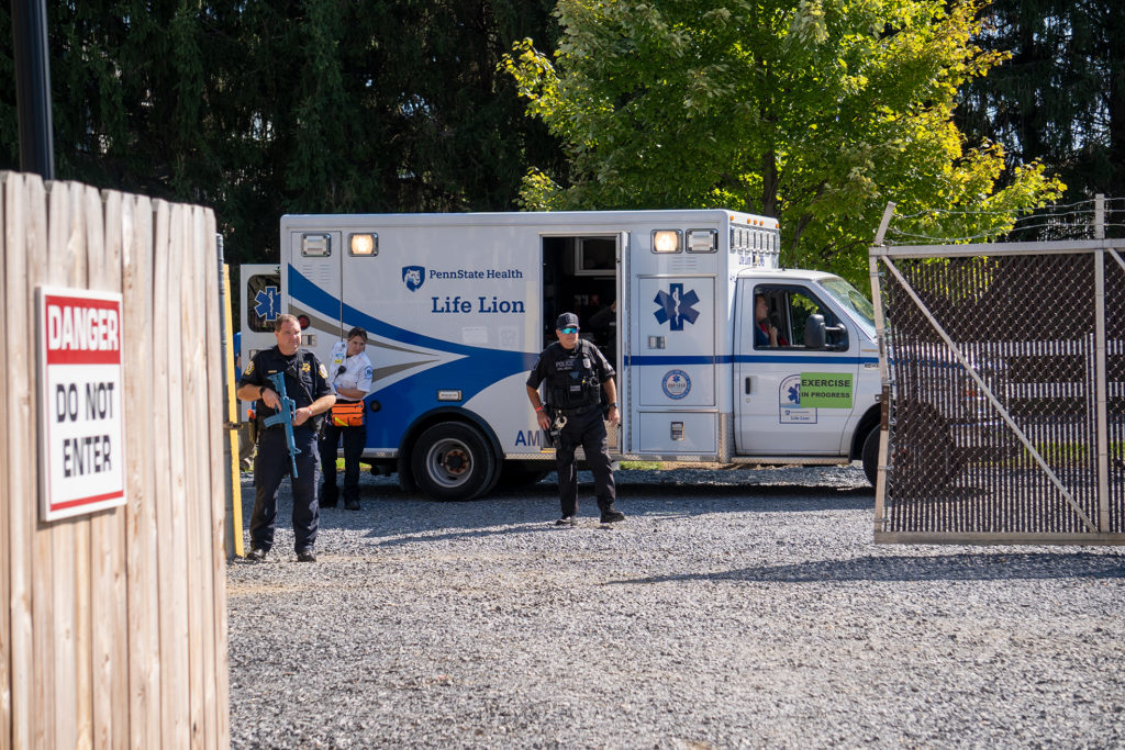 "Two officers armed with ""exercise"" weapons stand just outside of an open gate and in front of a Penn State Health Life Lion ambulance. A Life Lion staff member stands alongside the vehicle."