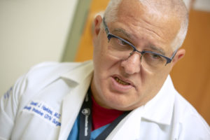 "Dr. Gerald Harkins is seen in a close-up as he talks. He has white hair and is wearing glasses and a lab coat with his name and ""Gyn Surgery"" on it.]"