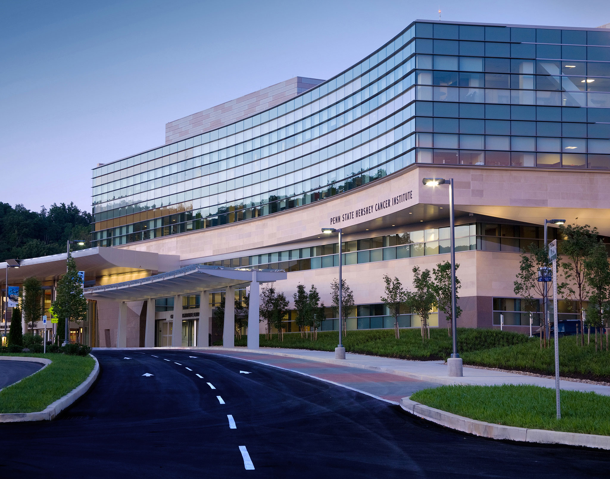 The front of Penn State Cancer Institute is seen with an empty road leading up to it.