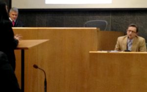 Dr. Mark Molckovsky sits in a witness stand and listens to a woman talking to him. He is wearing a suit and glasses. The woman is seen in profile and she is learning on a podium. A man with a robe, shirt and tie stands to the left of the judge's seat.