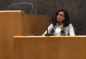 Dr. Alka Sood sits on a witness stands and speaks into a microphone. The witness stand is made of wood and is lower than the judge's seat to her left. She has shoulder-length hair and is wearing glasses, a blouse and a scarf.