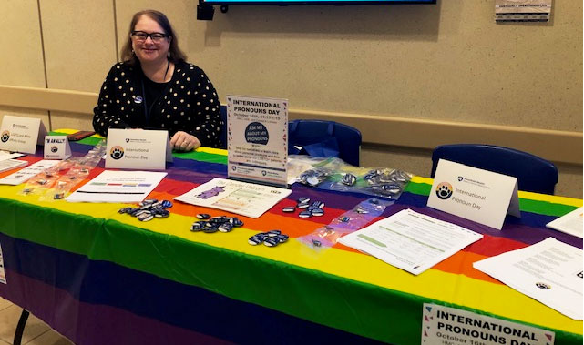 A smiling person is pictured in a lobby, sitting behind a table covered with a rainbow tablecloth displaying pins and handouts.