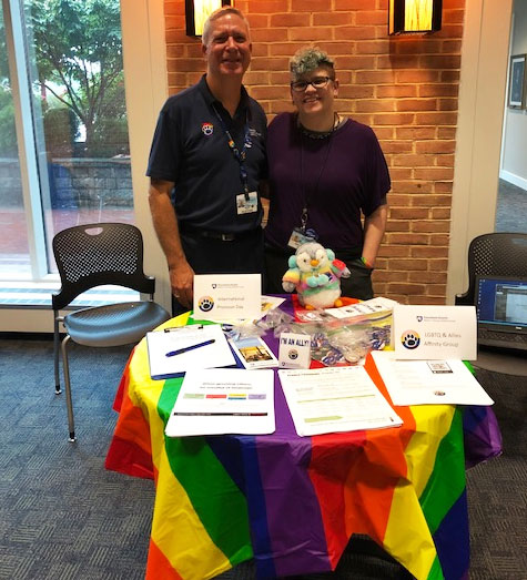 Two smiling people are pictured standing behind a table covered with a rainbow tablecloth. A rainbow stuffed penguin sits on the table, along with handouts and pins.