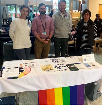 Four smiling people are pictured in a lobby, standing behind a table covered with a rainbow and white tablecloth displaying pins and handouts.