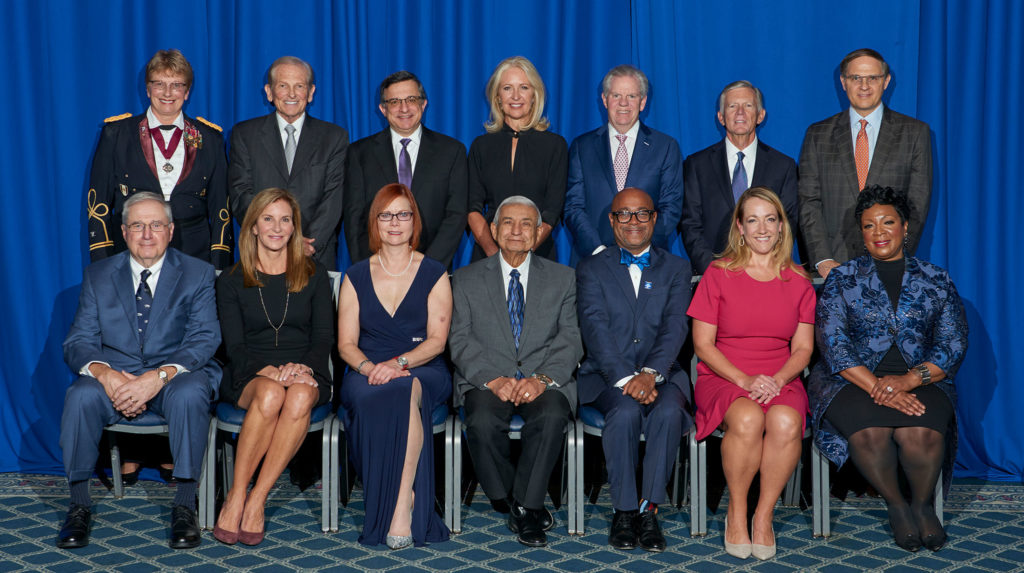 A group of 14 people are pictured, with one row of seven standing in the back and a row of seven seated in the front. They are Penn State's Alumni Fellow Award recipients for 2019.