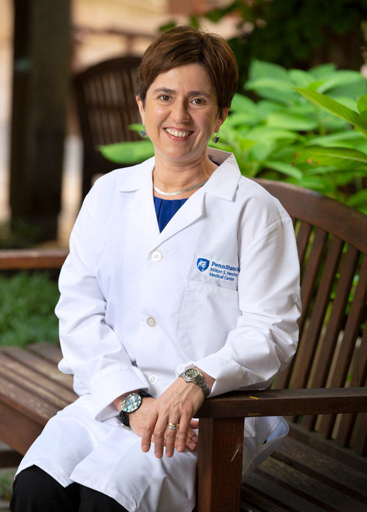 A woman in a medical coat sits on a bench in an outdoor garden, smiling professionally.