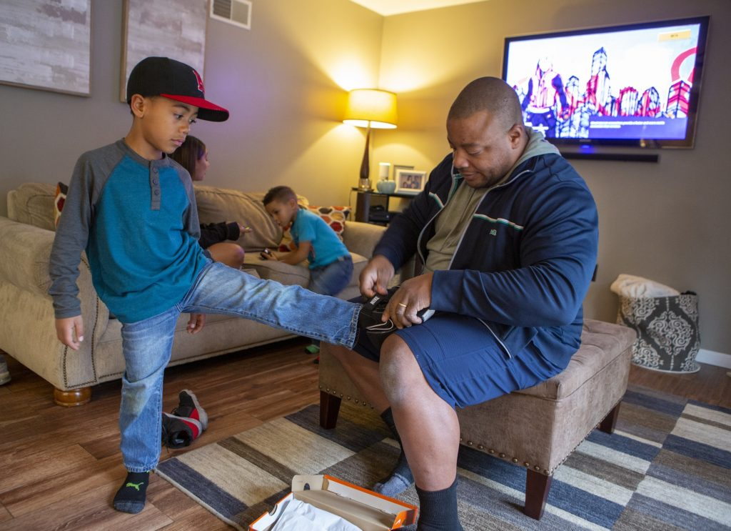 Jackson Doster, a 9-year-old boy, puts his foot on the lap of his father Rubin as Rubin looks at the size label inside the shoe. They are in a living room. Jackson is wearing a baseball cap, long-sleeved shirt and jeans. Rubin is wearing a jacket, sweatshirt and shorts. Behind them a girl sits on a couch and a three-year-old boy leans on the couch. A TV is on the wall behind them tuned to a show.
