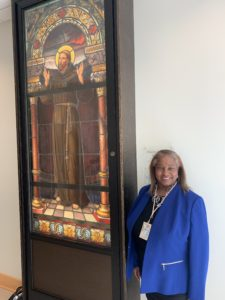Lynette Chappell Williams stands smiling next to a stained glass window.
