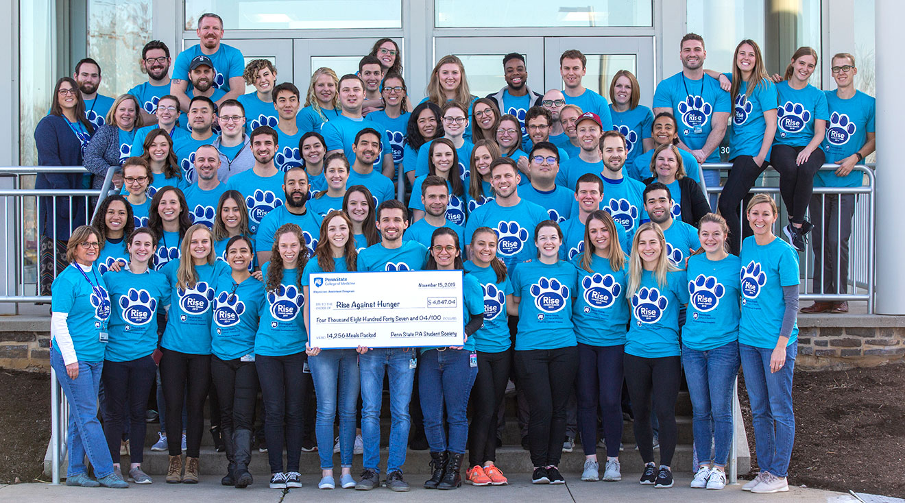 A large group of students and others, all wearing matching T-shirts, are seen standing in rows on the stairs leading into a building. People in the front row are holding a large ceremonial check.