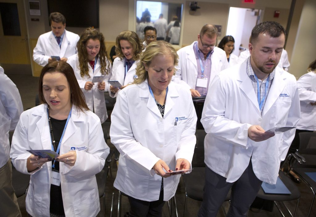 Eleven people stand in rows and read from cards at Penn State College of Medicine's Project Medical Education event. They are wearing white lab coats and lanyards with name badges. Behind them are a mirror and a doorway.