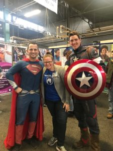 A woman smiles with two men dressed up as superheros