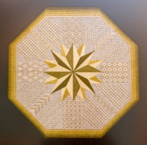 A closeup image of one of Dr. Daniel Hale's needlepoint pieces shows a many-pointed star in the middle of a design.