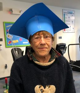 : Freddie Cadmus wears a graduation cap made from paper to mark the day she completed the Pulmonary Rehabilitation Program. She is standing in front of exercise equipment and wears a fleece sweatshirt and glasses.