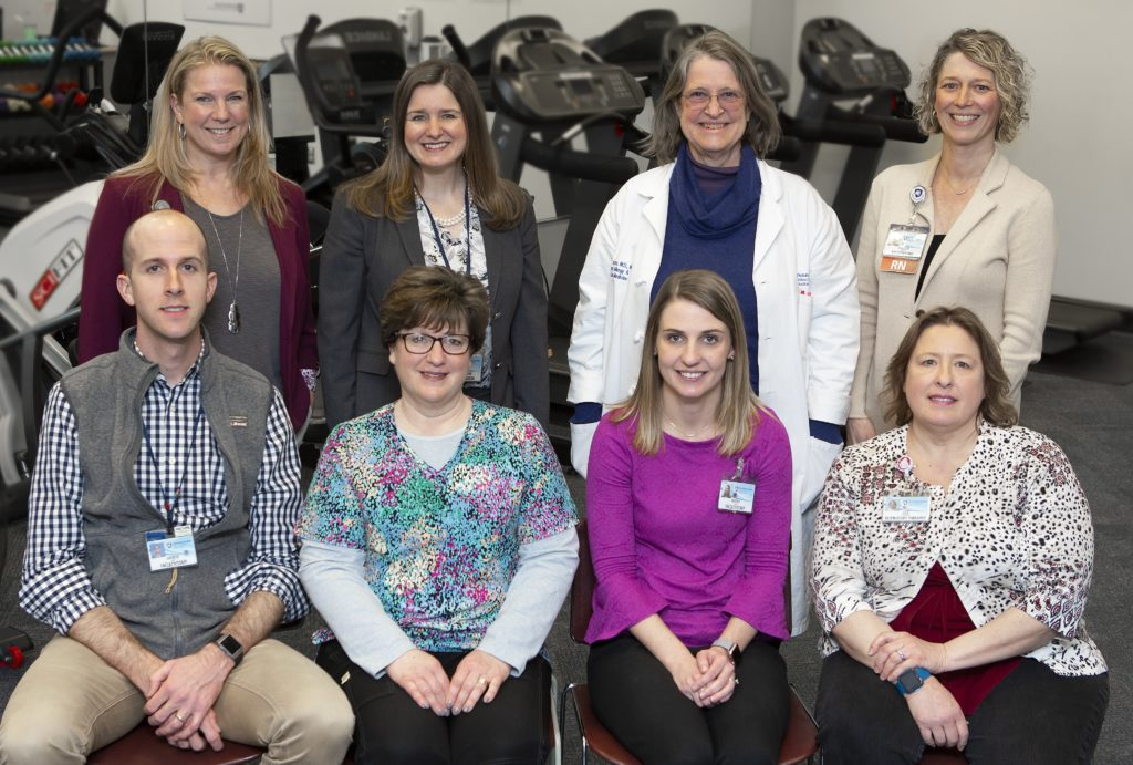 A group of eight people who are part of the Pulmonary Rehabilitation Program at Hershey Medical Center pose for a photo. Four people in the back row are standing, and four people in the front row at sitting. Behind them is a row of stair climbers and a mirror.