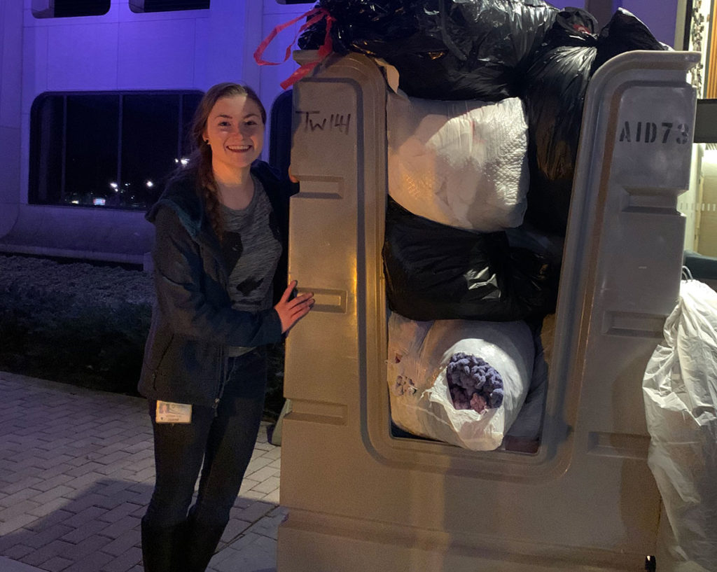 A young woman stands next to a large bin full of bags of winter coats.