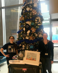 Two young women stand in front of a holiday tree in the lobby of Penn State Children's Hospital.