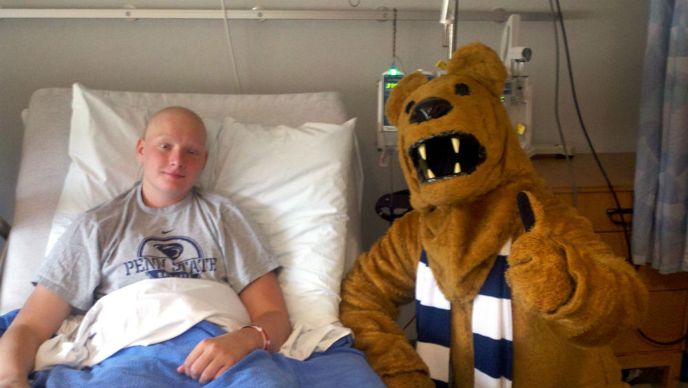 Colin Hayes sits up in bed at Penn State Health Children's Hospital in 2012. He is bald and is wearing a Penn State T-shirt. Next to him, the Nittany Lion mascot kneels and has his thumb up. The Lion is wearing a striped scarf.