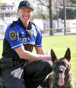 A police officer is pictured kneeling next to a police K-9 officer.