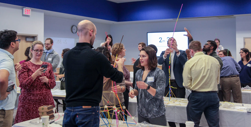A room full of students are seen building towers from materials such as straws and spaghetti.