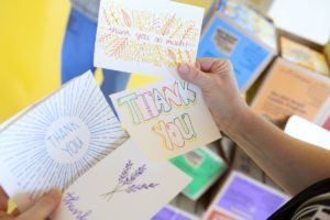 Image shows hands holding various Thank You cards