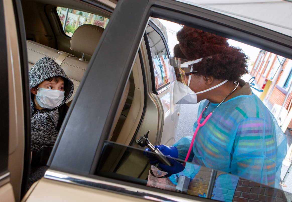 Dr. Desiree Webb, wearing a gown, face mask and stethoscope, stands next to a car with a boy who is wearing a face mask and jacket. The car door is open.